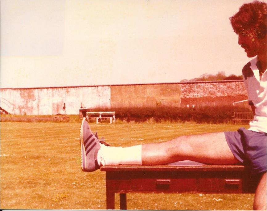 Picture of footballer sitting partially on table with one leg on the floor and one leg lifted toward himself with foot flat on the table