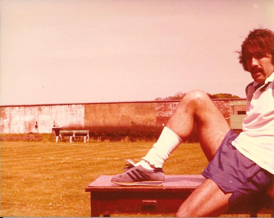 Picture of footballer sitting partially on a table with one leg raised horizontal across the table and the other leg vertical to the floor