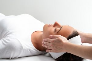Woman lying on physiotherapists couch receiving head massage
