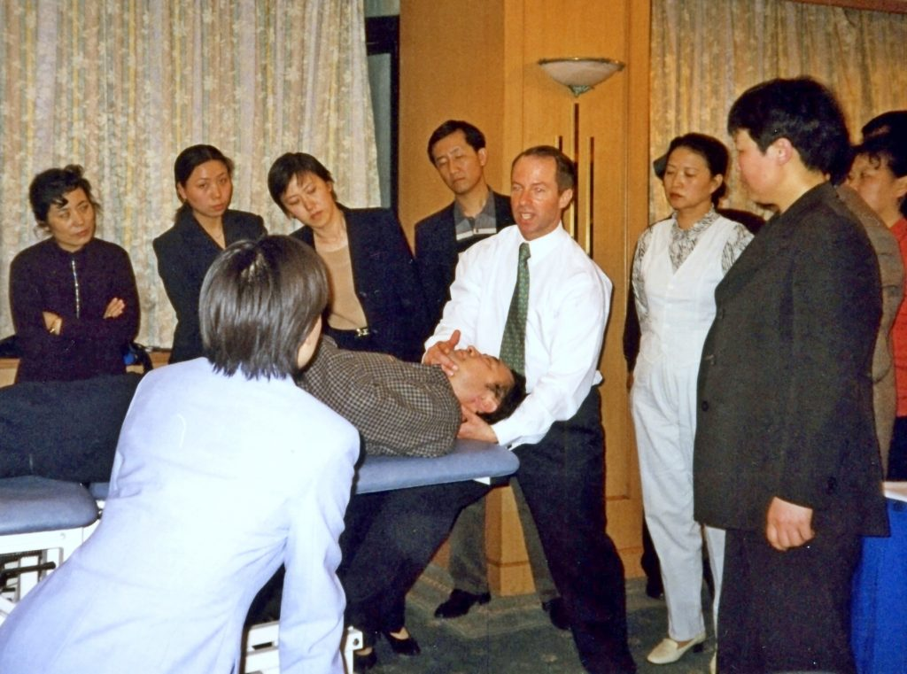 Picture of physiotherapist standing at the head of a man lying on physiotherapists table demonstrating manipulation technique with students watching o