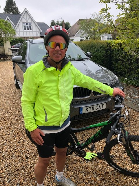 Picture of Physiotherapist Greg Welch standing next to his mountain bike in a high Vis jacket on the drive of the Talbot Therapy Clinic
