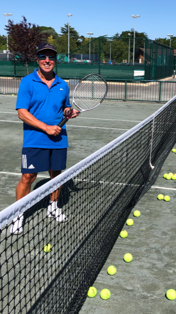 Picture of Physiotherapist Greg Welch on a tennis court holding a racket next to the net with a large number of teenis balls on the court