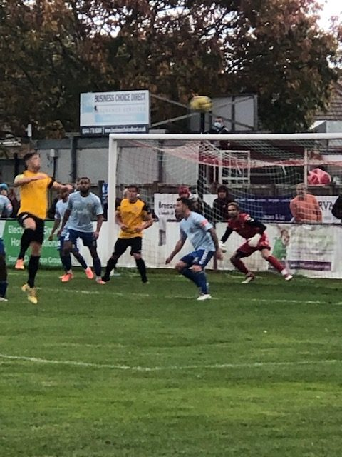Picture of footballers in front of the net, one going for a header at Poole Town FC