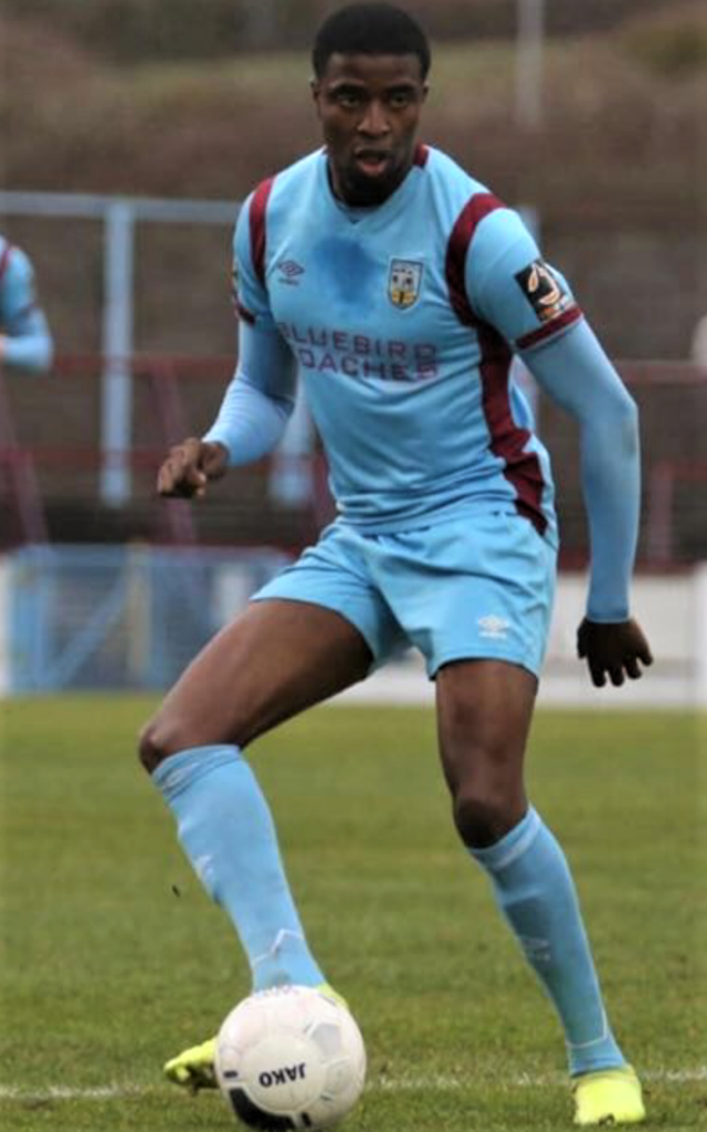 Picture of Weymouth footballer Ade Olumuyiwa in light blue kit taking a football on his right foot leaning slightly forward and sideways