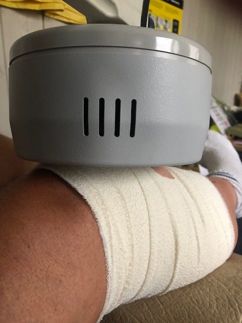 Picture of bandaged knee being treated with electrotherapy device